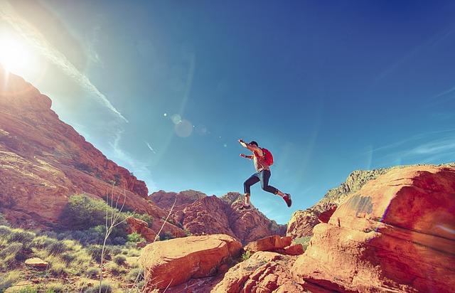 山の間を跳躍する男性