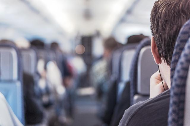 飛行機内の席に座る男性